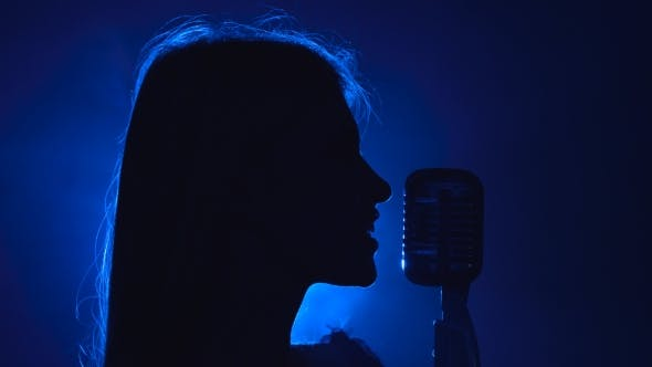 Thumbnail for Girl Sings in a Retro Microphone. Smoke Background. Silhouette. Side View.