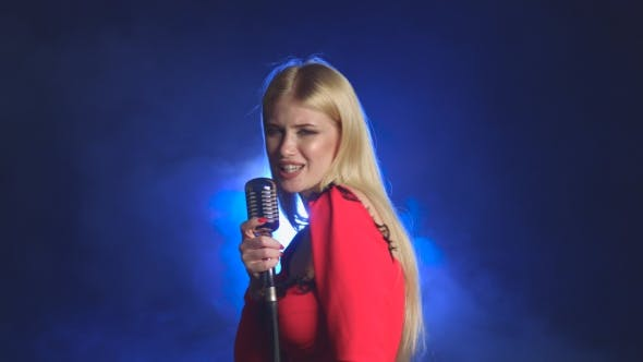 Thumbnail for Girl in a Red Dress Is Singing Into a Retro Microphone. Smoke Background