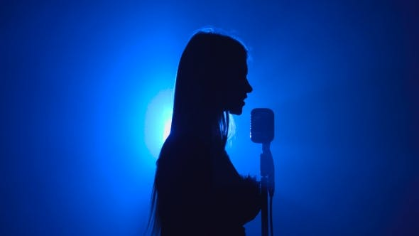 Thumbnail for Girl Sings Songs for the Clip. Smoke Background. Silhouette. Side View