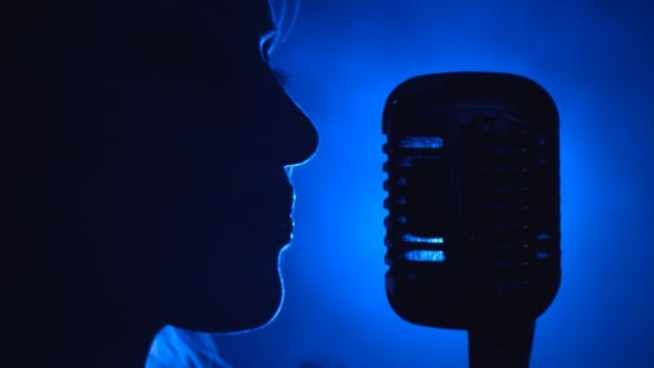Thumbnail for Singer Sings in a Retro Microphone. Smoke Background. Silhouette. Side View.