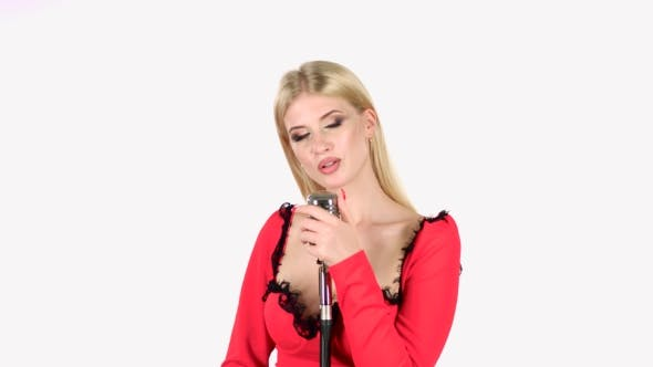 Thumbnail for Singer in a Red Dress Is Singing Into a Retro Microphone. White Background