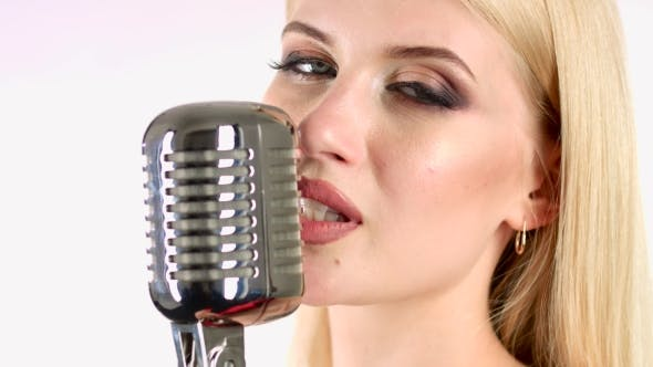 Thumbnail for Singer Sings in a Retro Microphone. White Background. Side View.