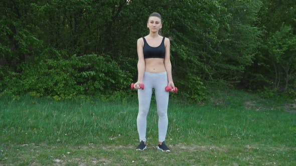Thumbnail for The Girl Is Exercising with a Dumbbell