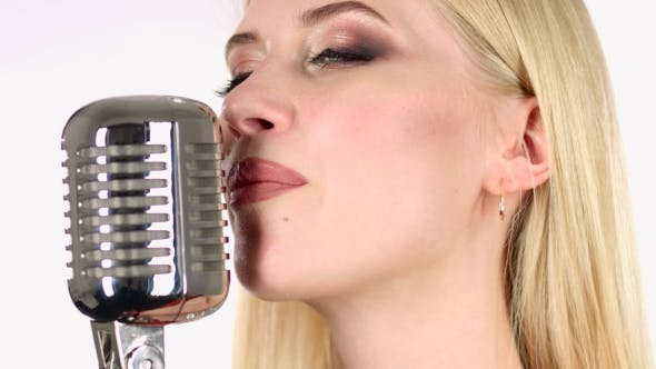 Thumbnail for Girl Sings in a Retro Microphone. White Background. Side View.