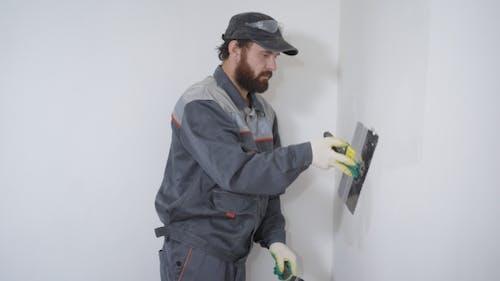 Arbeiter Kitt die Wand mit einem Spatel
