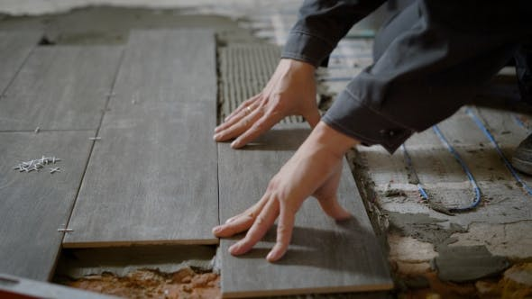 Schuss eines Bauarbeiters Verlegung von Keramikfliesen auf dem ebenen Boden in der Wohnung
