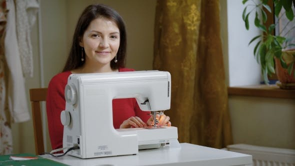 Thumbnail for Cheerful Adult Woman with Long Dark Hair Is Sitting at a Table with Sewing Machine