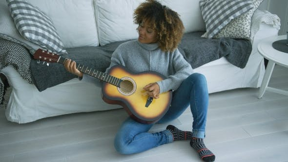 Thumbnail for Young Woman Playing Guitar at Home