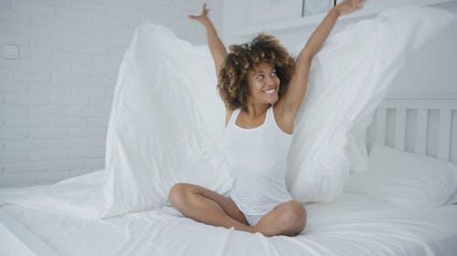 Happy Woman auf Bett mit Decke