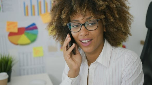 Cover Image for Young Woman Talking on Smartphone in Office
