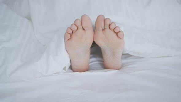 Thumbnail for Crop Female Feet Under Blanket