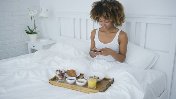 Thumbnail for Charming Woman Using Phone While Having Breakfast