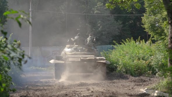Military Soldiers Sitting on War Tank Moving on Road at Shooting Range