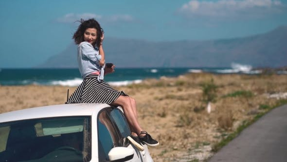 Thumbnail for Happy Brunette Girl Sitting on a Car at the Beach