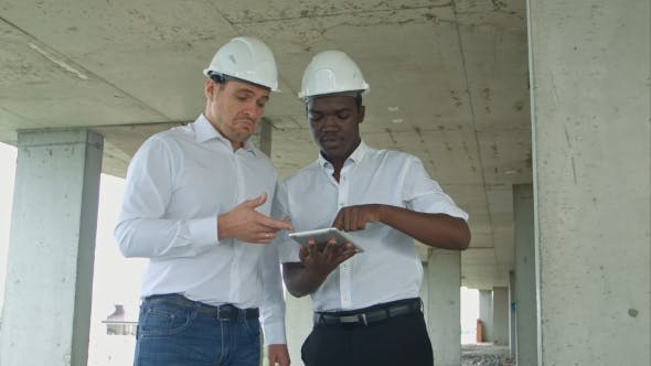 Thumbnail for African American Engineer and Caucasine Architect Using Digital Tablet and Wearing Safety Helmets at