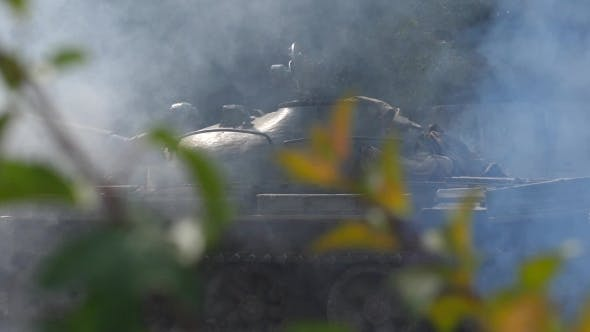 Military Tank with Smoke Moving on Battle Field