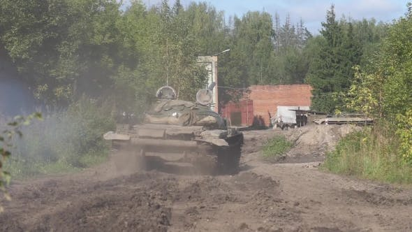 Military Tank Driving on Road on Background Destroyed Building