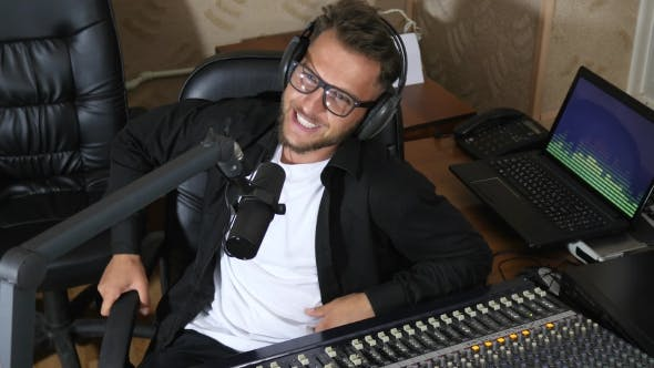 Thumbnail for Radio Presenter in Glasses Speaks Into Microphone Beside Mixing Console