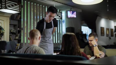 Waiter Serving Guests in Cafe