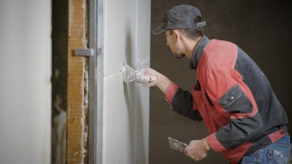 Thumbnail for A Professional Builder Who Holds a Spatula in His Hand, Applies a Grout on the Walls