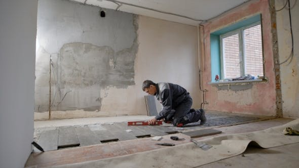 Thumbnail for a Builder Who Works in a Dwelling Places the Tile on the Floor and Checks the Slope and Evenness