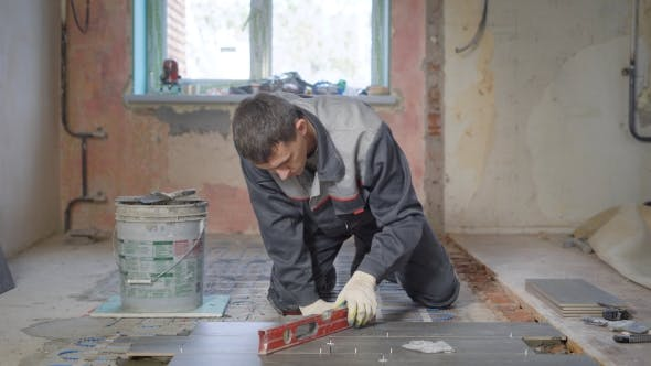 Thumbnail for The Worker in the Building Form Checks the Level of the Surface on the Ceramic-granite Tile