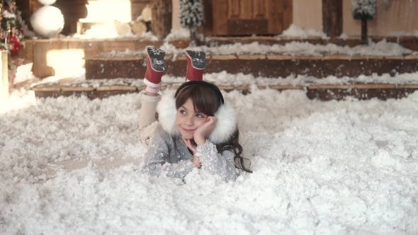 Thumbnail for Christmas or New Year. Child Fools Around and Lies in Artificial Snow