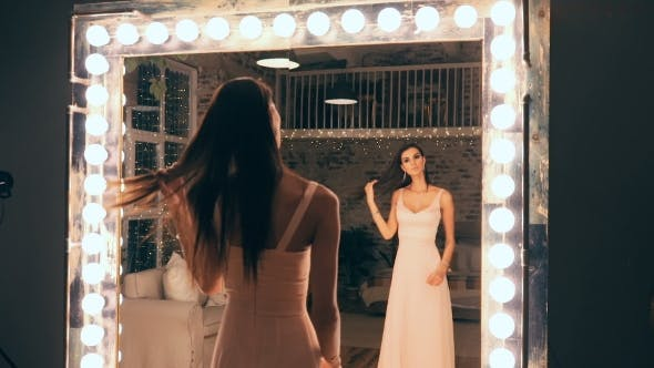 Thumbnail for Portrait of Elegant Girl in Evening Dress Posing in Front of a Mirror