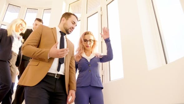 Cover Image for Business People Going Down on Stairs in Office Building with Big Windows