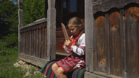 Thumbnail for Little Girl Is Sitting on the Porch of the House