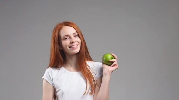 Thumbnail for Portrait of Young Redhead Girl Holds Up a Green Apple