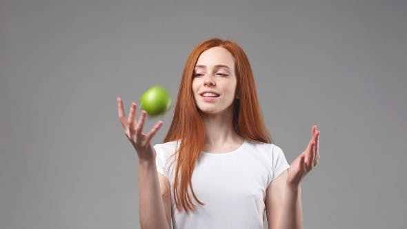 Thumbnail for Young Redhead Girl Tosses Green Apple.