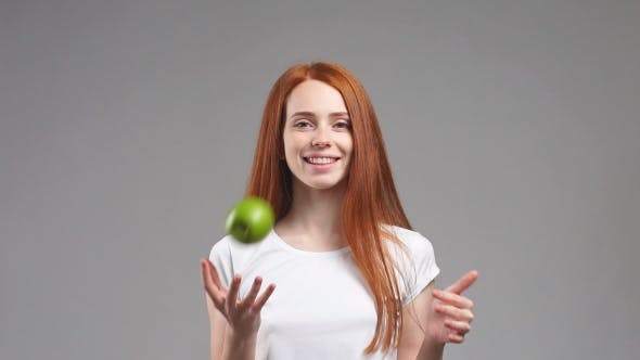 Thumbnail for Beautiful Redhead Girl with a Green Apple in Hands Smiling on White Background.