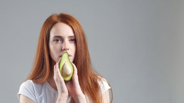 Thumbnail for Girl Sniffing Avocado and Showing It at Camera on the White Background.