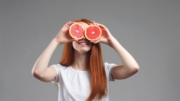 Thumbnail for Young Happy Woman Is Holding Slices of Grapefruits To Her Eyes on White Background.