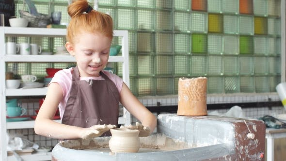 Thumbnail for Happy Kid Is Pressing a Clay Vase on Wheel, Kid Is Working at Pottery Wheel Slowly