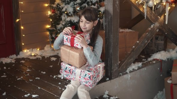 Thumbnail for Christmas or New Year. Little Girl Holding in Hands a Box with Gifts and Smiles