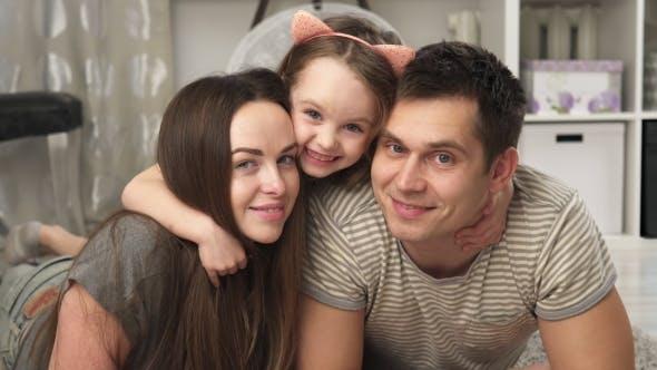 Thumbnail for Happy Little Girl Hugs her Parents