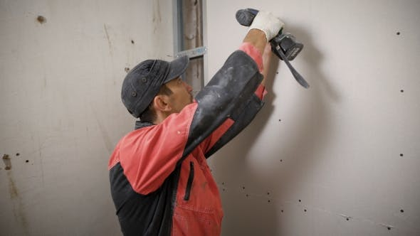 Thumbnail for Builder in Uniform Installing Panels on Wall Using Electric Drill