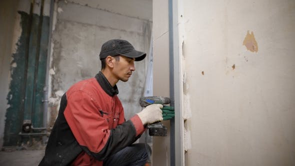 Man Using Tool Fixing Overlaps on Wall in Building
