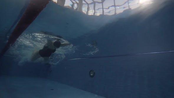 Female Swimmer Floating Butterfly Stroke in Blue Water Pool Underwater View