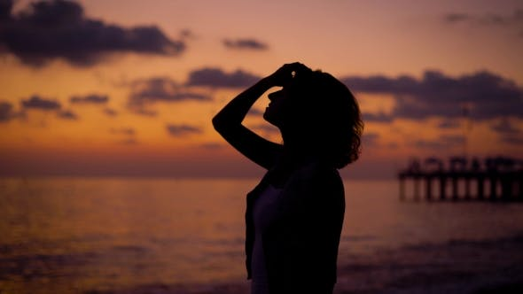 Thumbnail for Silhouette of Woman Is Standing on a Sea Shore in Twilight on a Background of Sunset Sky