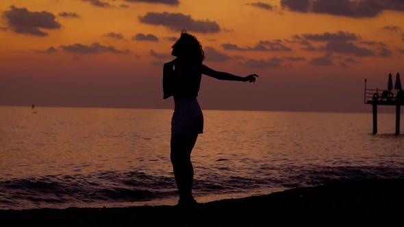 Thumbnail for Silhouette of Happy Slim Woman Is Jumping on a Sea Coast in Evening Time After Sunset and Rising