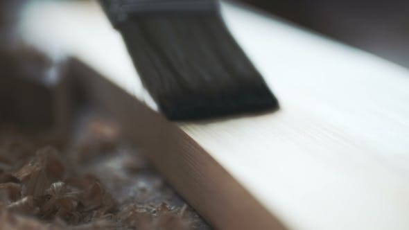 Thumbnail for Young Man Painting Wooden Board with a Brown Paint