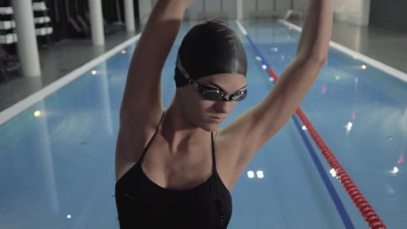 Swimmer Put on Goggles and Make Stretching Exercise on Background Swimming Pool