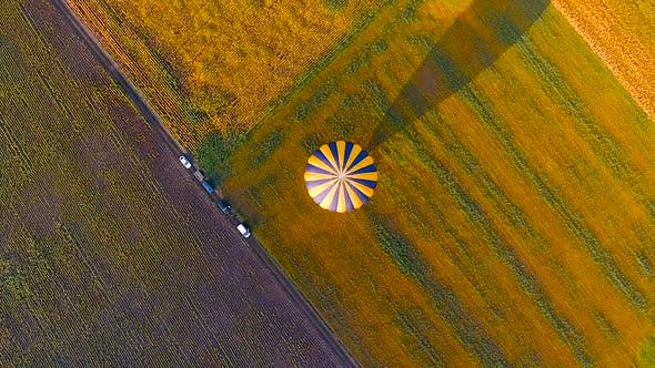 Thumbnail for Envelope of Hot Air Balloon Landed Floating in Air, Casting Shadow Over Field