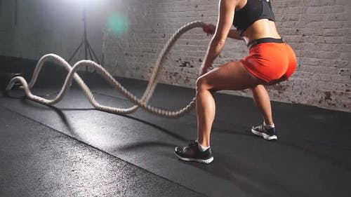 Battling Ropes Girl at Gym Workout Exercise Fitted Body. Slow Motion