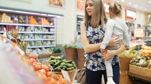 Mum with Small Daughter Choose Products in Big Marketplace