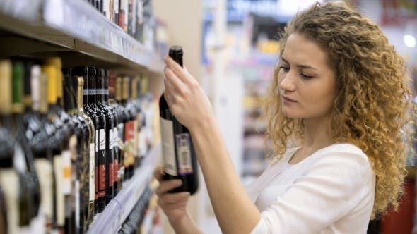 Thumbnail for Beautiful Woman Chooses and Buying Wine In The Supermarket