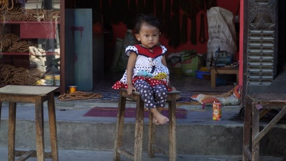 Thumbnail for Little Cute Little Girl Is Sitting on a Chair